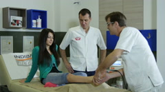 Two male physiotherapist massaging injured ankle of female patient with massager - stock footage