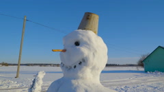 A small pail on the snowmans head - stock footage