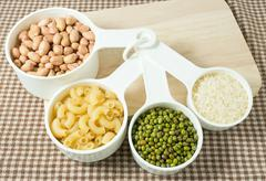Foods High in Carbohydrate, Raw Pasta, Rice, Peanuts and Mung Beans in Plasti - stock photo