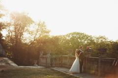 Beautiful romantic wedding couple of newlyweds hugging near old castle on sunset Stock Photos
