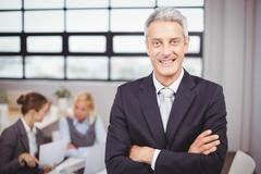 Happy confidence businessman with colleagues in background - stock photo
