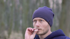 Close-up of a guy who smokes a cigarette. Slowly Stock Footage