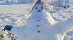 Big fat snowman with bonnet on the head - stock footage