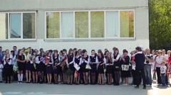 Novosibirsk, Russia  September 1, 2015. School line is in schoolyard with pupils Stock Footage