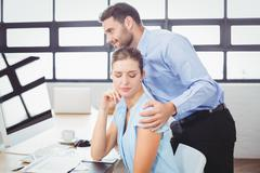 Businessman harassing female colleague at computer desk Stock Photos