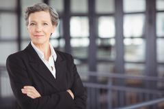 Confident businesswoman standing by railing - stock photo