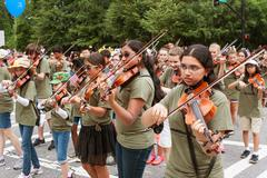 Youth Violin Players Perform While Walking In Old Soldiers Parade - stock photo