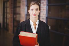 Confident female lawyer with book standing in office - stock photo