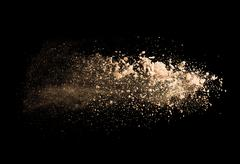 Explosion of brown powder on black background - stock photo