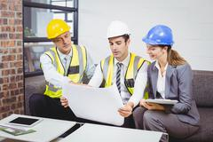 Architects discussing with blueprint Stock Photos