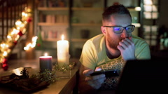 Man looking unhappy and texting on smartphone in his christmassy house - stock footage