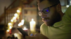 Pensive man texting on smartphone while sitting at his christmassy house - stock footage