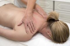 Masseuse giving a massage to a female client Kuvituskuvat