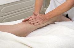 A masseuse massaging a clients leg Kuvituskuvat