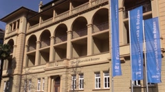 Free University of Bolzano-Bozen - Old building with flags - three languages Stock Footage