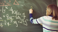 Teacher writing numbers on blackboard and having a lecture - stock footage