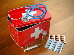 First aid kit with stethoscope, pills and syringe on the table. - stock illustration