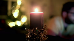 View of christmassy candle and man in the background, steadycam shot - stock footage