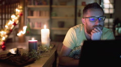 Man relaxing at his christmassy house and browsing internet on laptop Stock Footage
