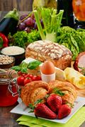 Composition with variety of organic food products on kitchen table - stock photo