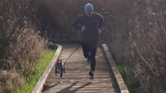 Young Man and Boston Terrier Dog Jogging Up Nature Boardwalk Stock Footage