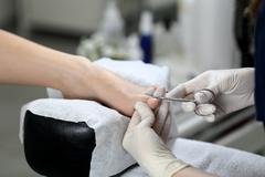 Cutting cuticle on foot, nail scissors - stock photo