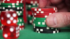 Red dice and casino chips in fingers on green table Stock Footage