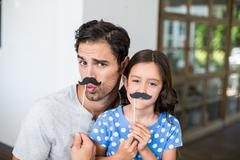 Portrait of father and daughter with artificial mustache Stock Photos