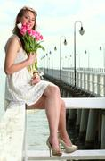 Smiling woman with bunch of flowers sea - stock photo