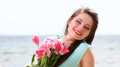 young beautiful woman portrait on the beach bunch flower - stock photo