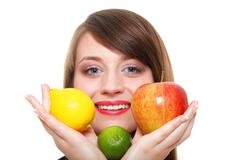 Young smiling woman with fruits and vegetables white background - stock photo