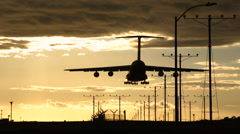 Military Cargo Jet Airplane Landing At Sunset at the Airport Stock Footage