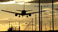 Passenger Jet Airplane Landing At Sunset at the Airport Stock Footage