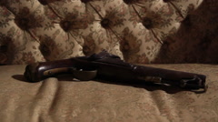 Ancient gun over old couch dolly Stock Footage