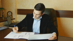 Young businessman working with documents at desk in office Stock Footage