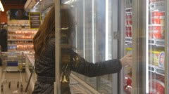 Young woman buying dairy or refrigerated groceries at the supermarket - stock footage