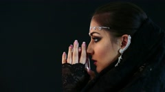 Pretty oriental woman in abaya on black background Stock Footage