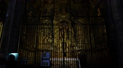 Dim illuminated apse iconostasis at Barcelona Cathedral, tilt down shot. Stock Footage