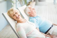 High angle view of senior couple relaxing on lounge chair - stock photo
