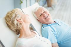 High angle view of happy senior couple relaxing on lounge chair - stock photo