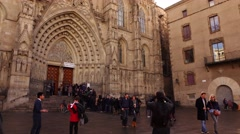 People stand in queue in front of Barcelona Cathedral, tilt up shot. - stock footage