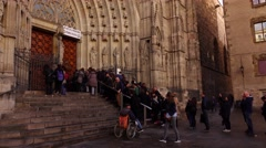 Many tourists stand in queue to closed entrance of Gothic Cathedral Stock Footage