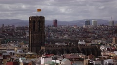 Strong Gothic bell tower rise above crowdy city, cloudy sky, Senyera flag on top Stock Footage