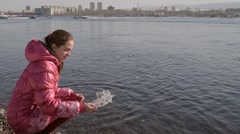 Woman dropping piece of ice into river Stock Footage