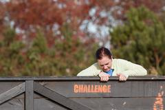 Woman Struggles Pulling Herself Over Wall At Obstacle Course Race - stock photo