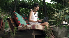 Young beautiful woman with laptop, relaxing and drinking in cafe in the garden Stock Footage