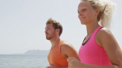 Running Young Couple In Sportswear Jogging by Sea - People Doing Sport Stock Footage