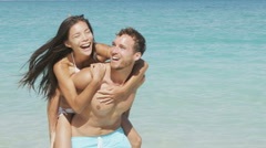 Couple beach vacation fun - happy piggyback love - stock footage
