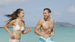 Happy couple having fun laughing on beach vacation Stock Footage