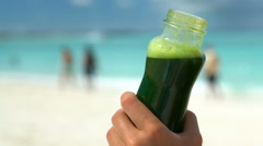 Hand Holding Vegetable Smoothie Bottle On Beach - Healthy Diet Detox Juice Stock Footage